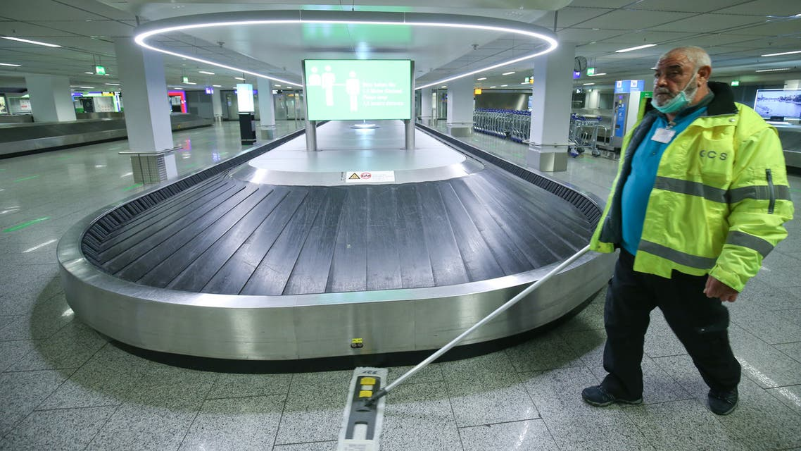 A staff member cleans the area near a baggage belt as the International airport presents additional COVID-19 safety measures, amid the coronavirus disease outbreak in Frankfurt, Germany, May 12, 2020. REUTERS/Ralph Orlowski