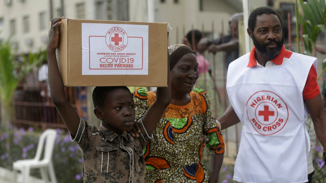 A child with his mother from Makoko Slum, carries their food parcel distributed by the Nigerian Red Cross, provided for those under coronavirus related movement restrictions, in Lagos, Nigeria on April 25, 2020. (AP)