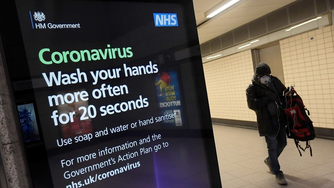 A man in a protective face mask walks past a British government public health campaign advertisement at Victoria underground station, as the number of coronavirus (COVID-19) cases grow around the world, London, Britain. (Reuters)