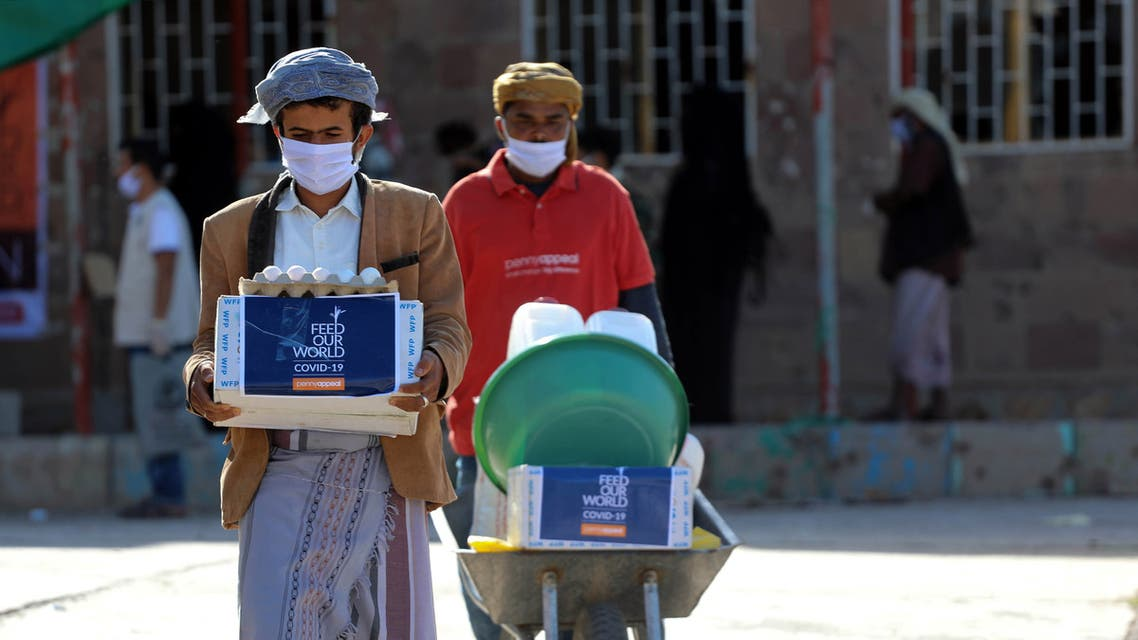 Men wearing protective masks receive humanitarian aid in Yemen's third city of Taez, on May 8, 2020, amid the novel coronavirus pandemic crisis. Yemen has suffered years of war that have driven millions from their homes and plunged the country into what the United Nations describes as the world's worst humanitarian crisis.