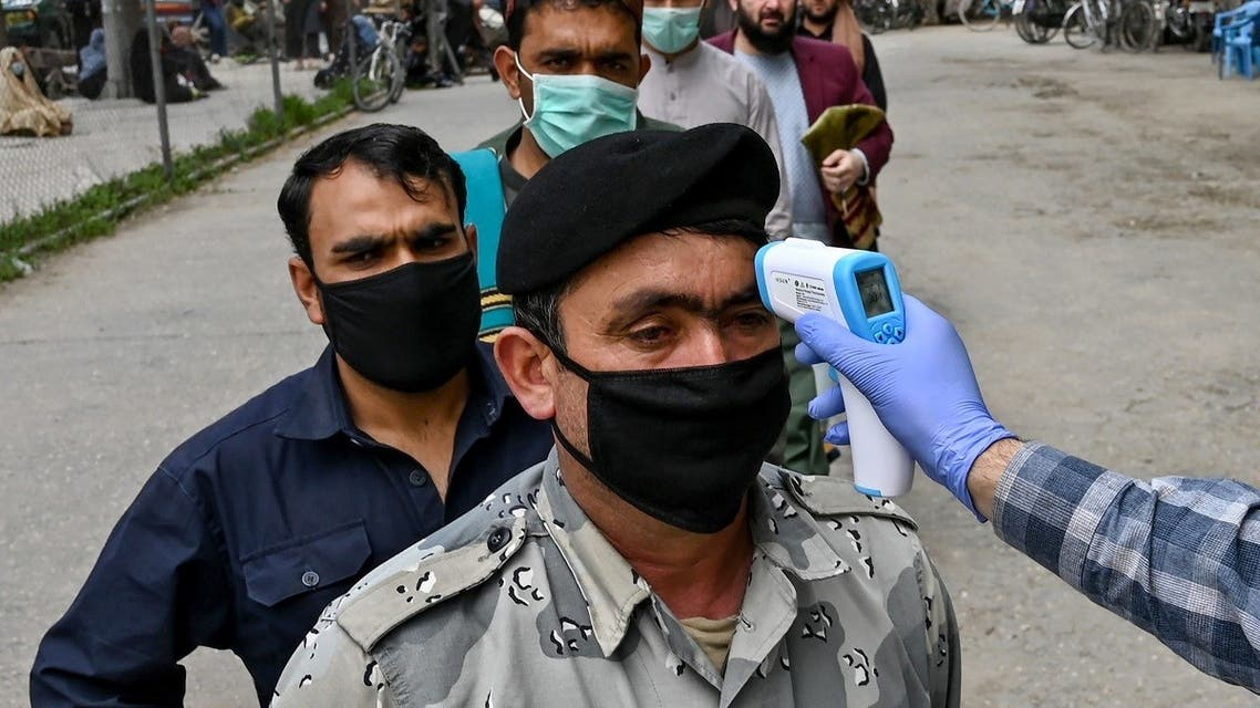 In this file photo taken on April 24, 2020 a health worker (R) checks the body temperature of a devotee before the Friday prayers on the first day of the Muslim holy month of Ramadan at Wazir Akbar Khan mosque in Kabul. (AFP)
