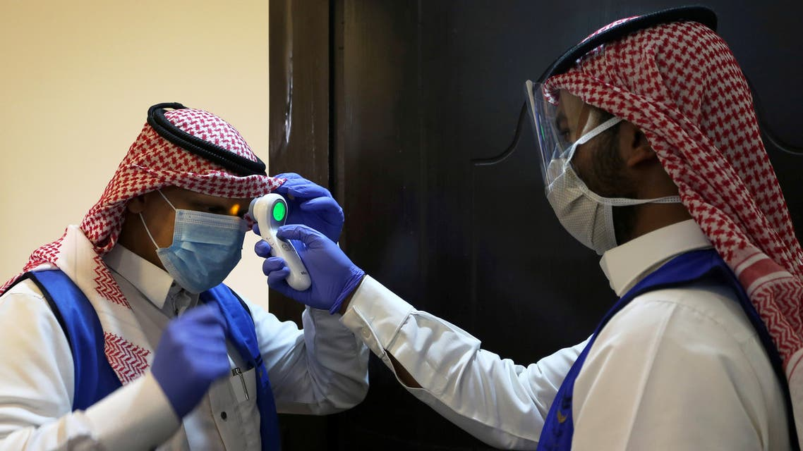 A Saudi volunteer supervisor wearing a protective face mask and gloves checks the temperature of another volunteer before preparing boxes of Iftar meals provided by a charity organisation following the outbreak of the coronavirus disease (COVID-19), during the holy month of Ramadan, in Riyadh. (Reuters)