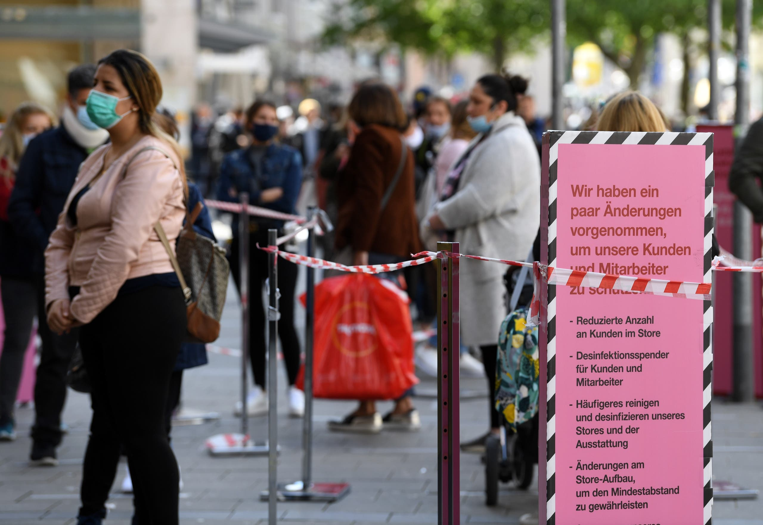 Customers wait in line after the coronavirus lockdown was eased around Germany, in Munich, Germany, May 12, 2020. (Reuters)