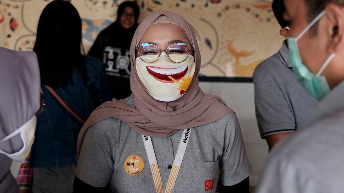 An employee wearing a face mask as a precaution against the new coronavirus outbreak shares a light moment with colleagues at a McDonald's restaurant in Jakarta, Indonesia. (AP)