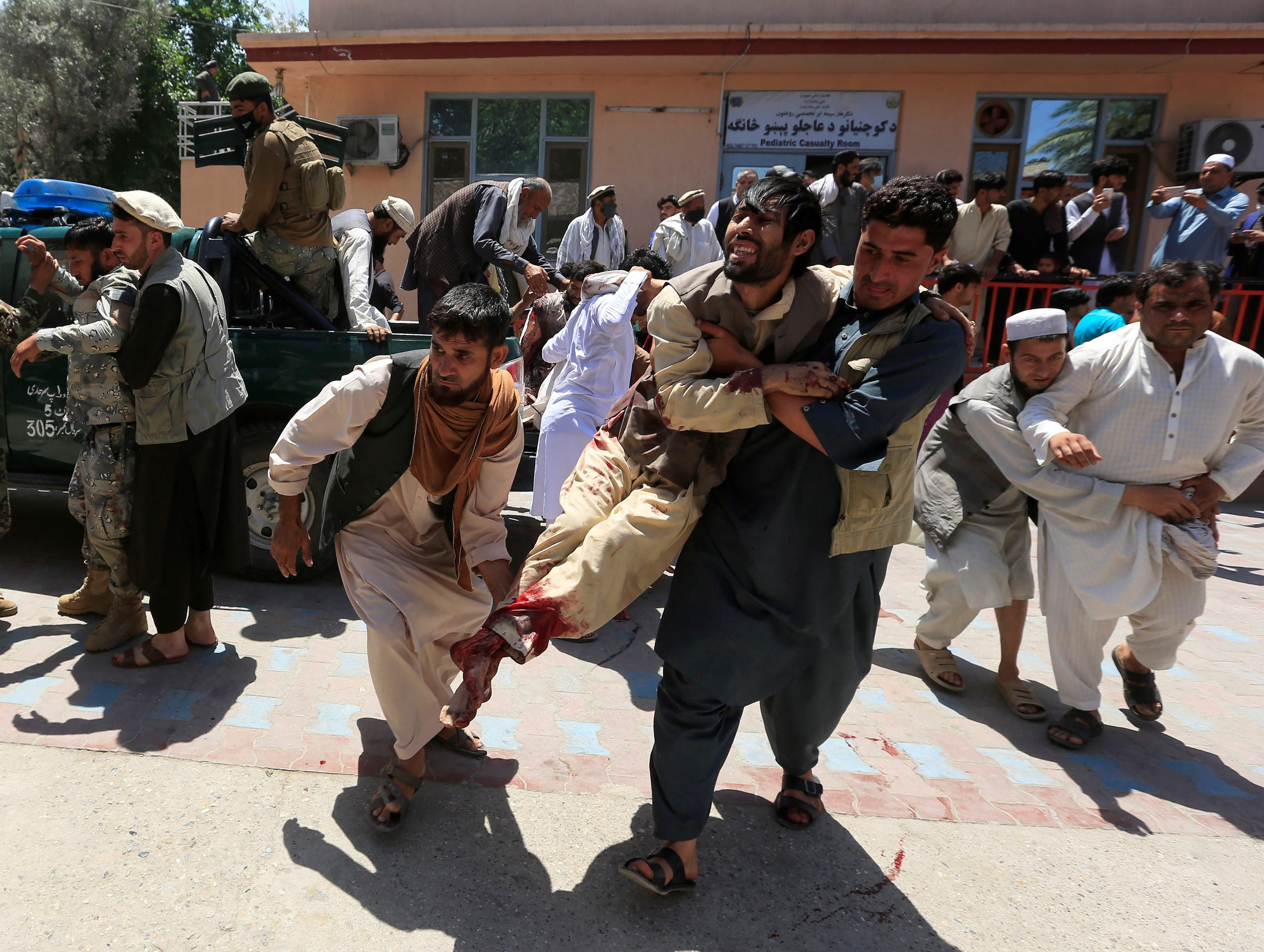 Men carry an injured person to a hospital after a blast during a funeral ceremony in Jalalabad, Afghanistan May 12, 2020.  (Reuters)