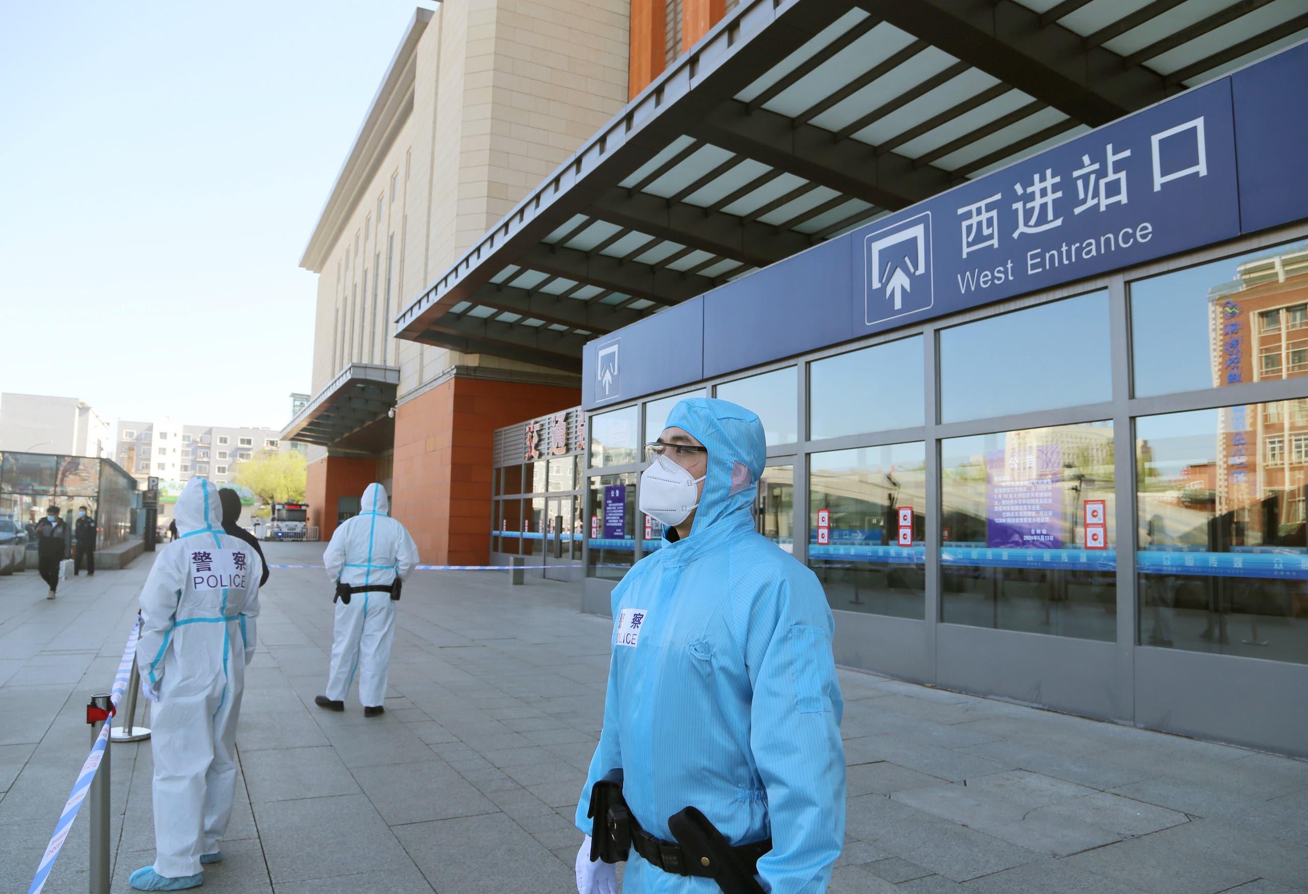 شرطي يحرس محطة قطارات مغلقة بسبب تفشي كورونا في منطقة جديدة بالصين