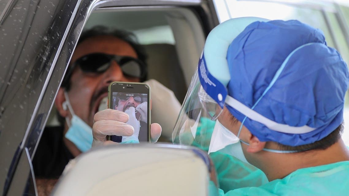 A health worker, wearing personal protective equipment, collects a swab sample from a man at a drive-thru testing service for COVID-19 coronavirus in the Qatari capital Doha. (AFP)