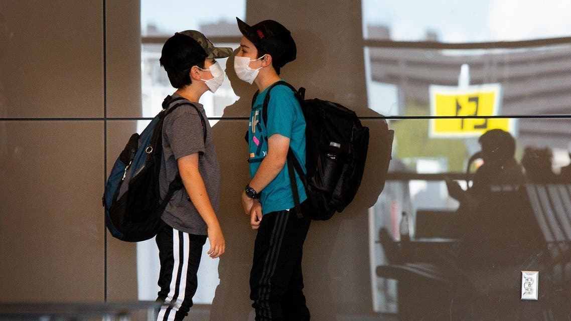 Kids play while wearing protective face masks at the Phoenix International Airport on March 14, 2020 in Phoenix, Arizona. (AFP)
