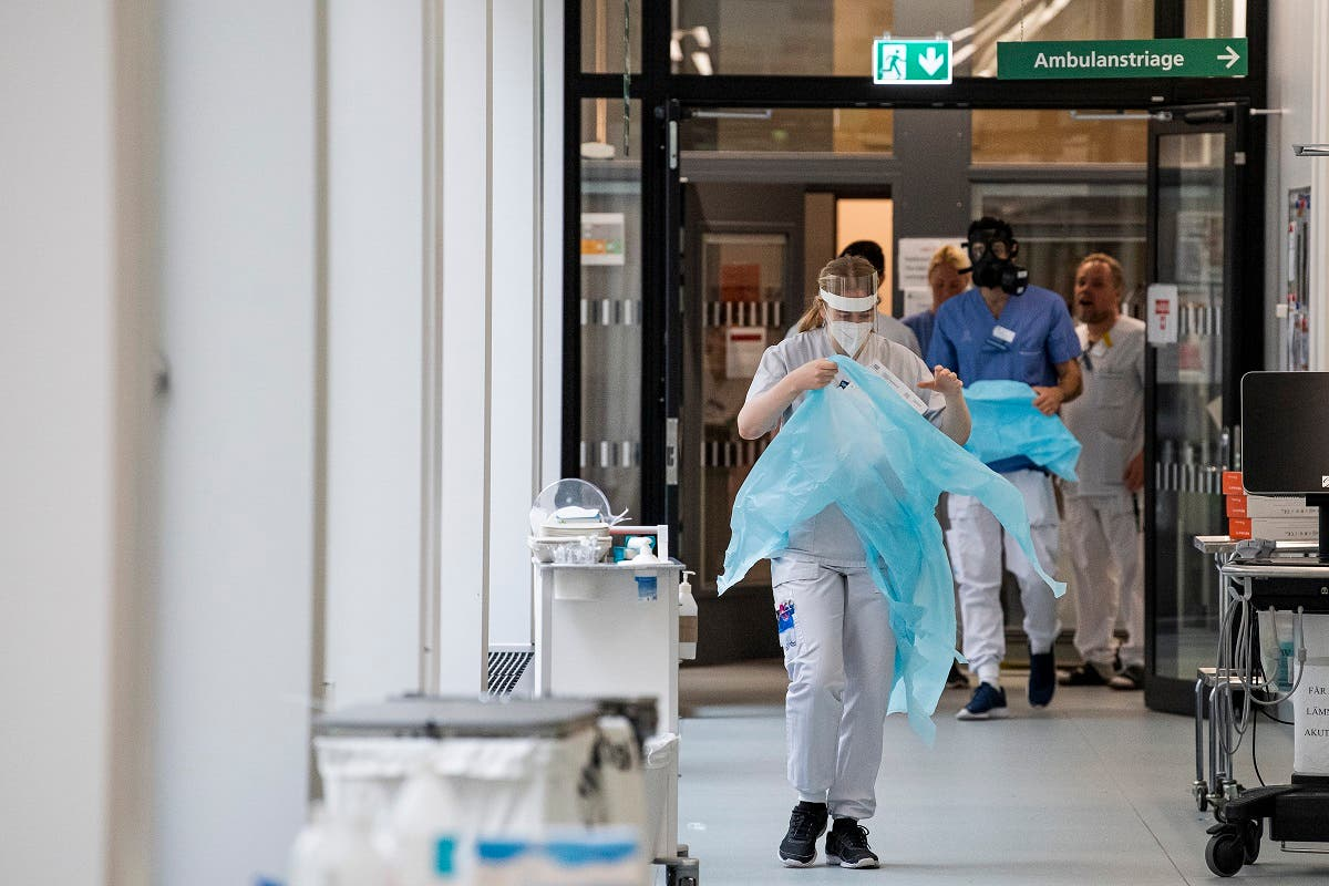 Healthcare workers put on protective gear as they prepare to receive a patient at the Intensive Care Unit at a hospital near Stockholm on May 13, 2020, during the coronavirus pandemic. (AFP)