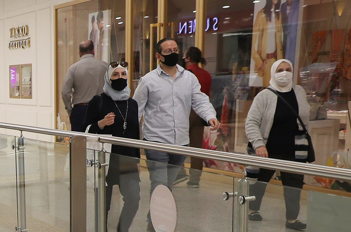 People wearing protective face masks walk inside a shopping mall on May 11, 2020 in Ankara, on the first day of reopening of shops which has been closed since March 21 due to the coronavirus. (AFP)
