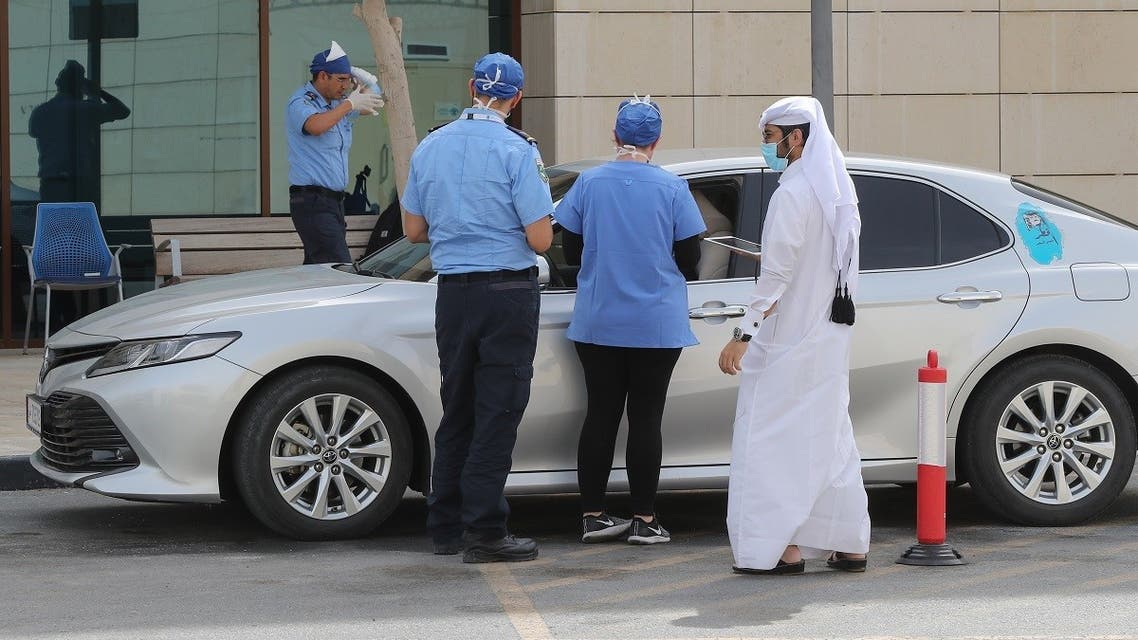 Health workers assist at a drive-thru testing service for COVID-19 coronavirus in the Qatari capital Doha, on May 7, 2020. (AFP)