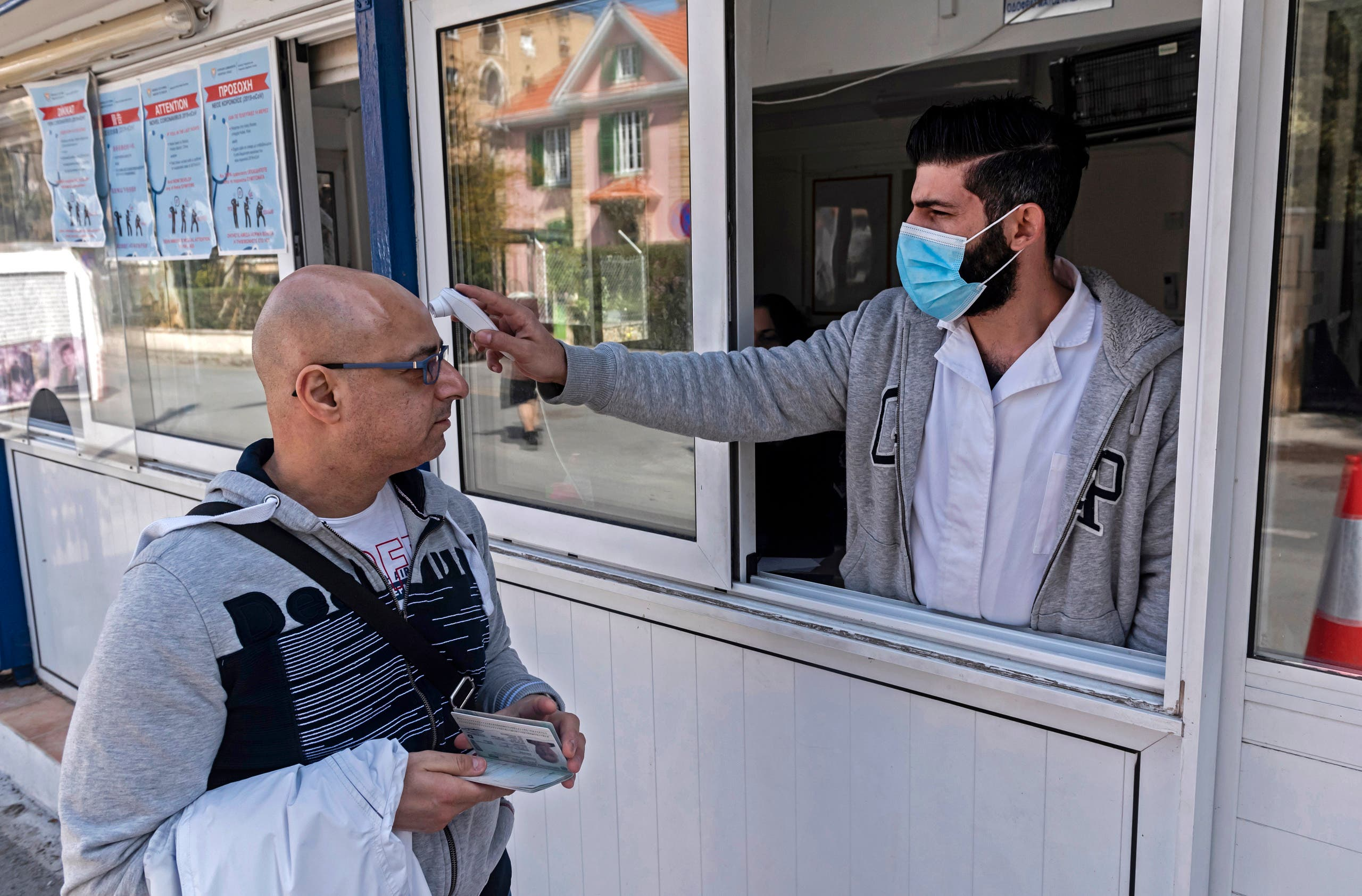 In this file photo taken on March 04, 2020, a Cypriot medic checks the temperature of a man crossing the Ledra Palace checkpoint in Nicosia. (File photo: AFP)