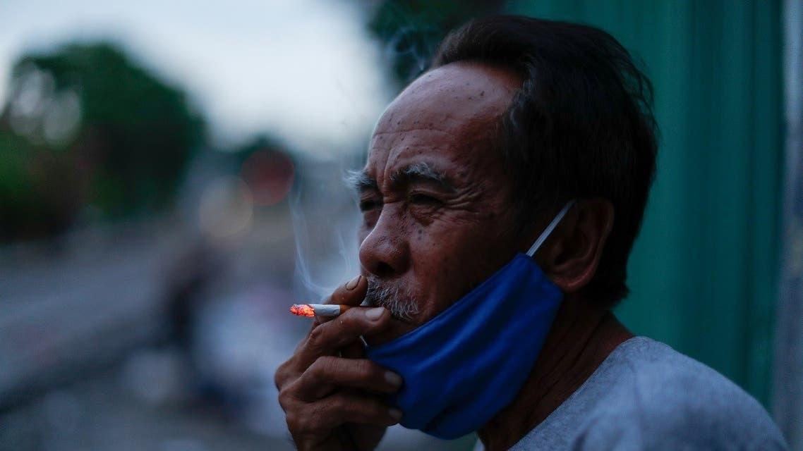 A man wearing a protective mask smokes a cigarette near the tracks in a slum, amid the coronavirus disease (COVID-19) outbreak, in Bangkok, Thailand. (Reuters)