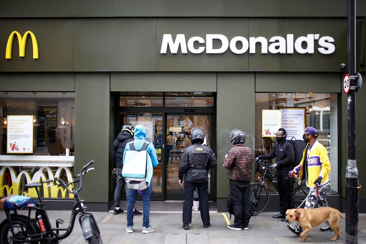 Delivery men are seen outside a reopened McDonald's with take-out only deliveries in Dalston, following the outbreak of the coronavirus disease (COVID-19), London. (Reuters)