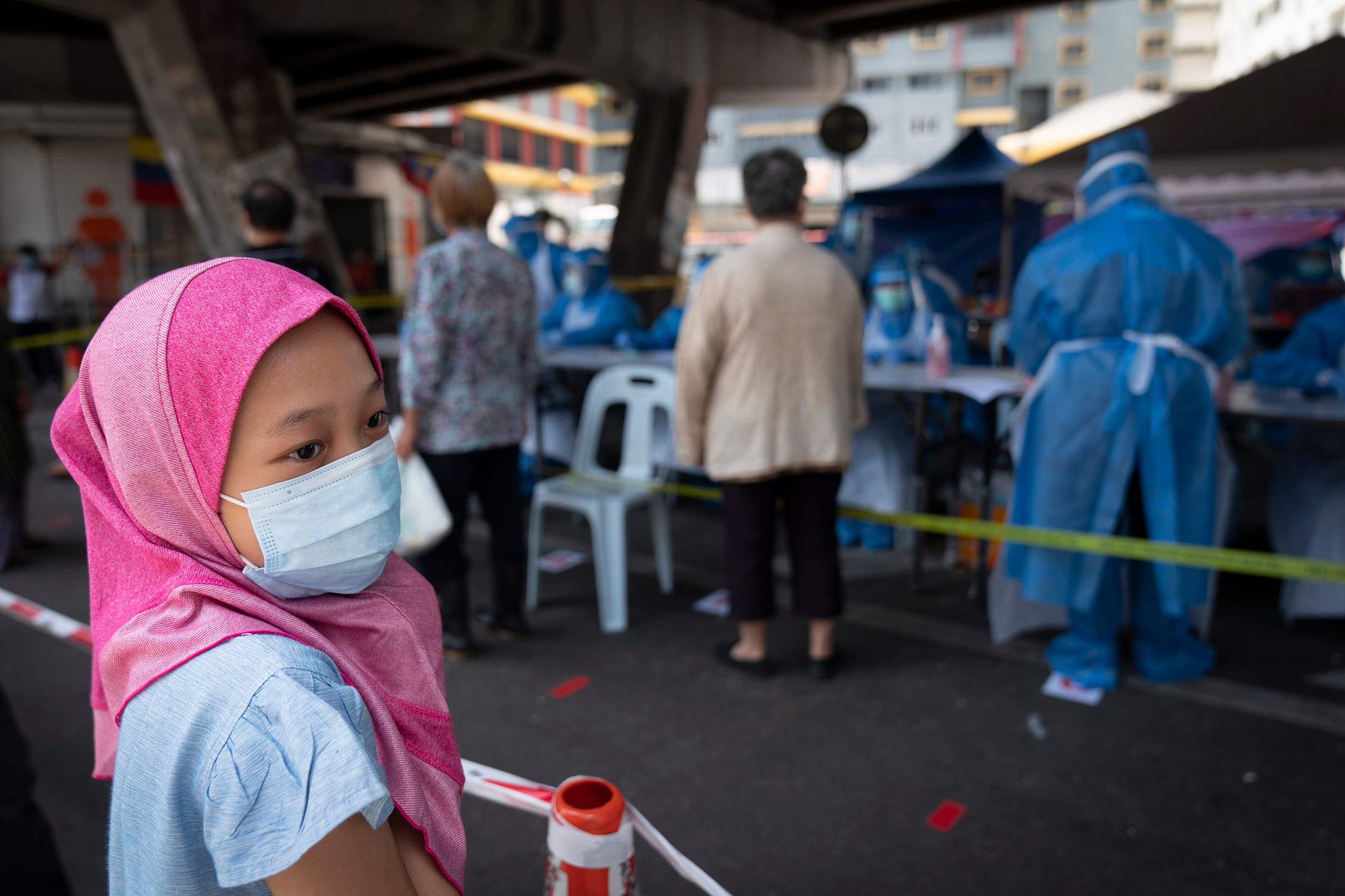 A Muslim girl wearing a face mask waits for new coronavirus testing at a wet market in Kuala Lumpur, Malaysia May 5, 2020. (AP)