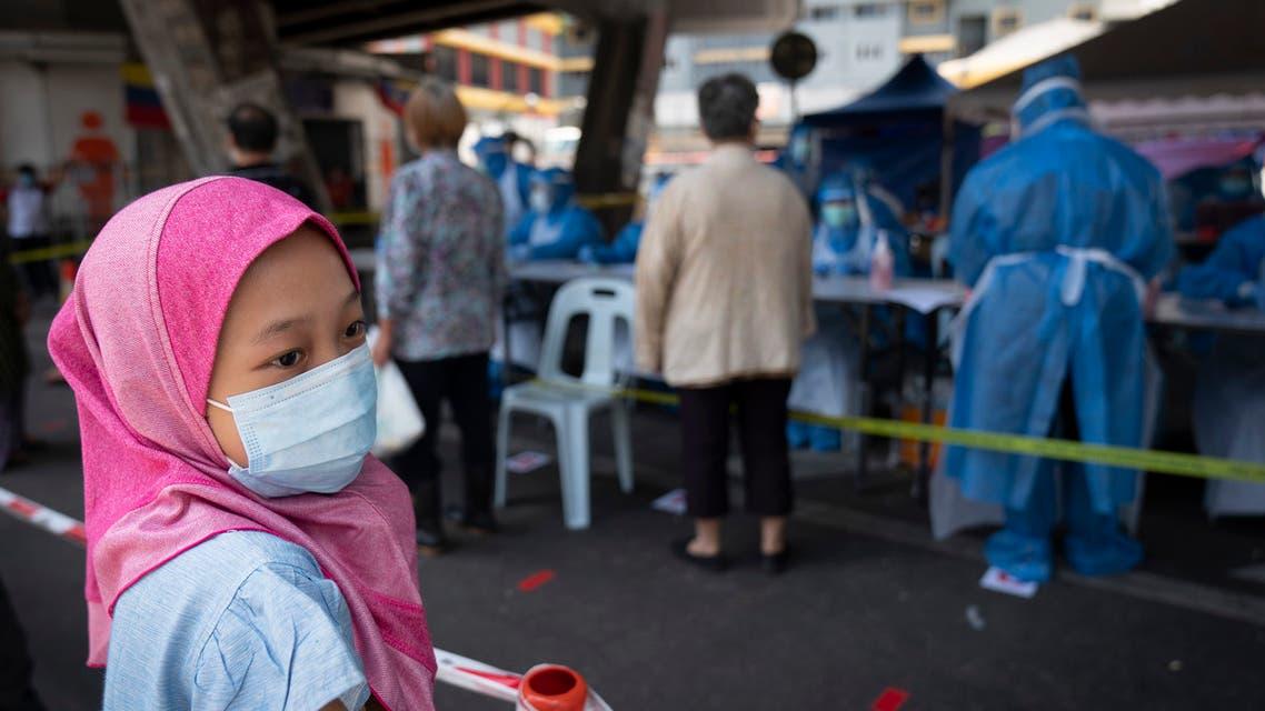A Muslim girl wearing a face mask waits for new coronavirus testing at a wet market in Kuala Lumpur, Malaysia May 5, 2020. (AP)