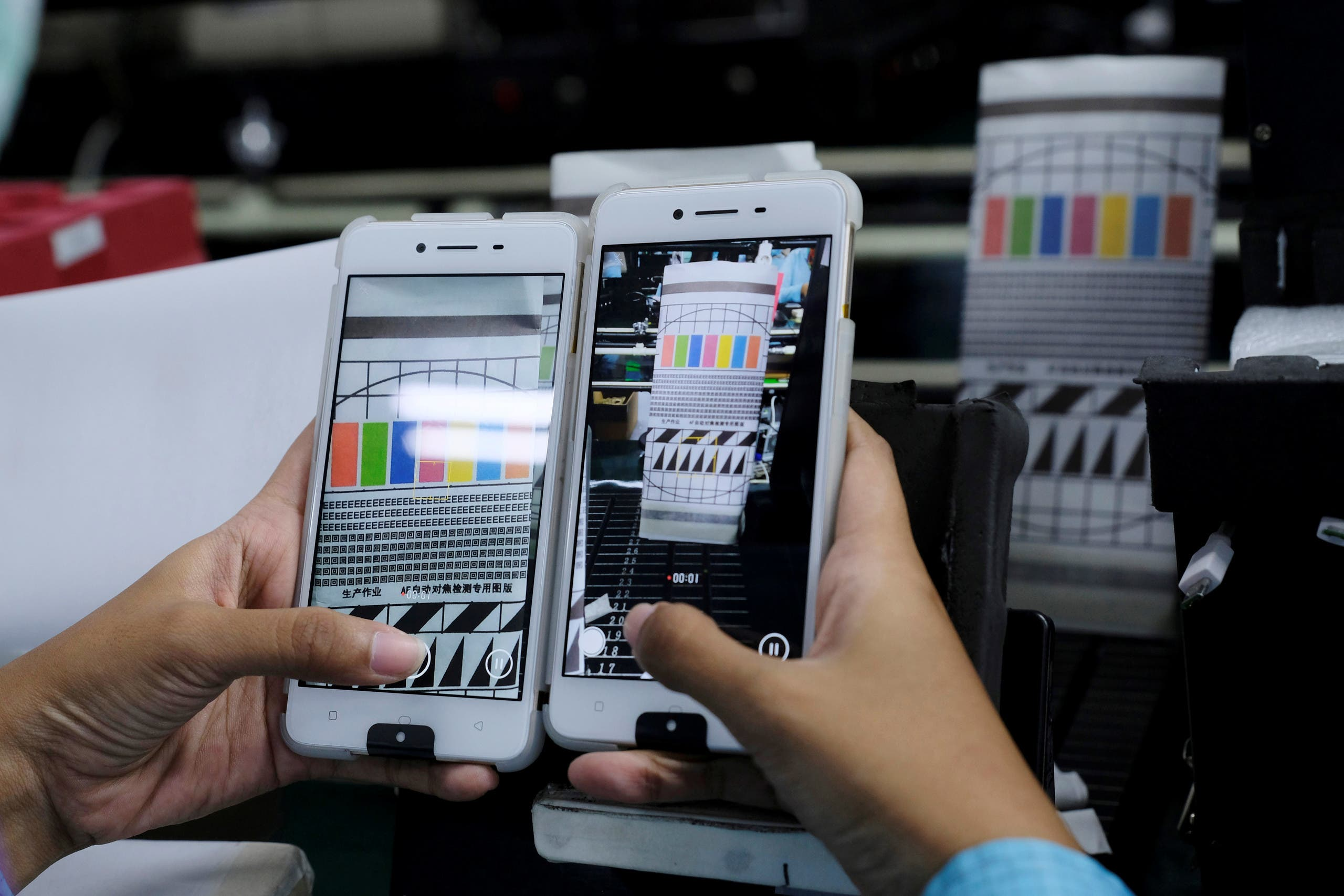 A worker conducts a color test on OPPO F1s smartphones at an OPPO smartphone factory in Tangerang, Indonesia.(Reuters)