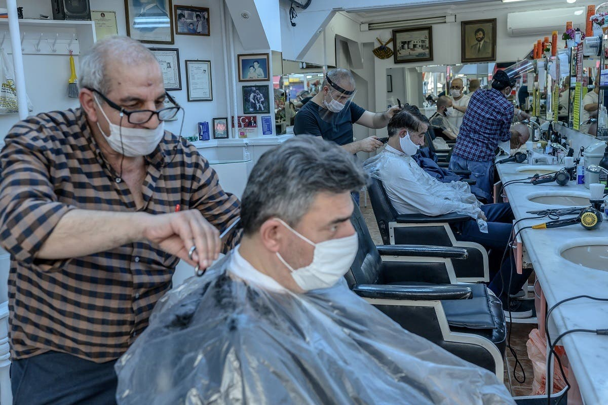 Barbers, wearing protective face masks cut the hair of clients in a barber shop in Istanbul on May 11, 2020. (AFP)