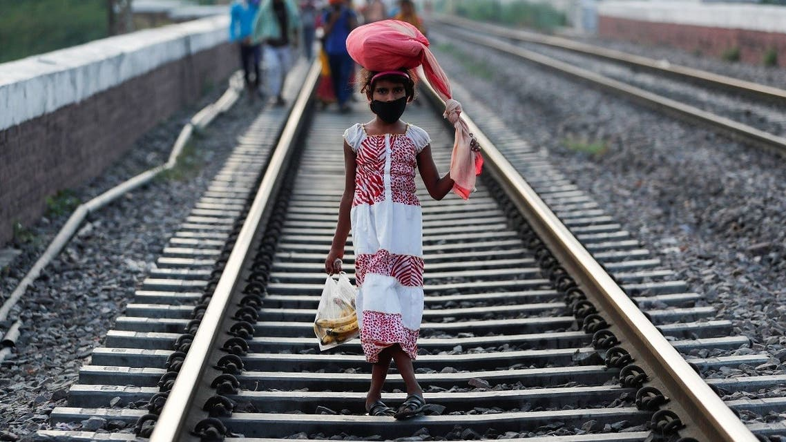 The daughter of a migrant worker carrying her belongings walks along a railway track to return to her home state of eastern Bihar. (Reuters)