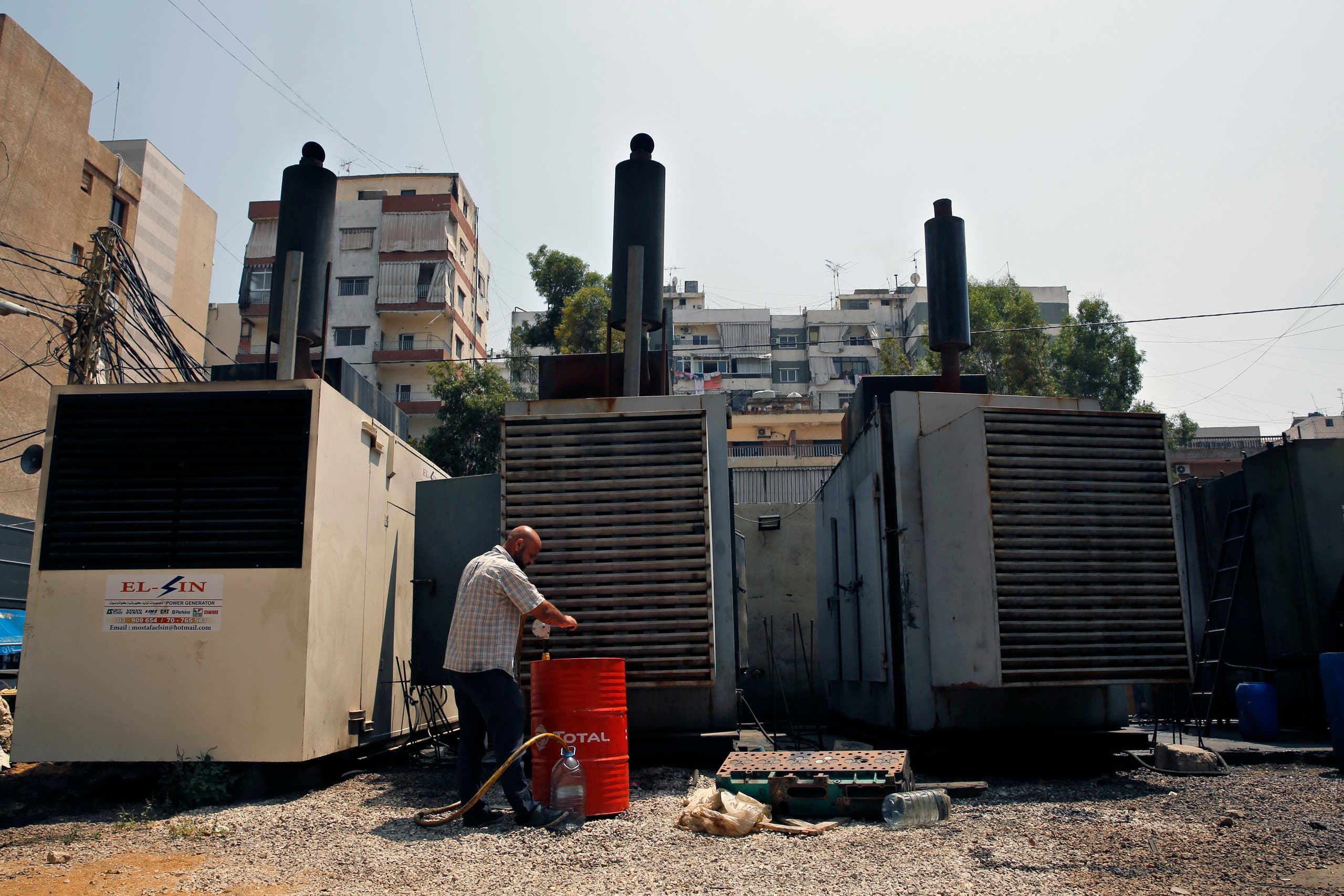 This Monday, July 16, 2018, photo shows Mamdouh al-Amari oiling privately-owned diesel generators that provide power to homes and businesses, in the southern suburbs of Beirut, Lebanon. (AP)
