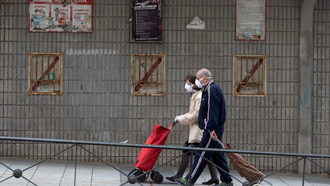 A couple walk past the closed stadium of Spanish 2nd division club Rayo Vallecano in Madrid, Spain, on Thursday, May 14, 2020. (AP)