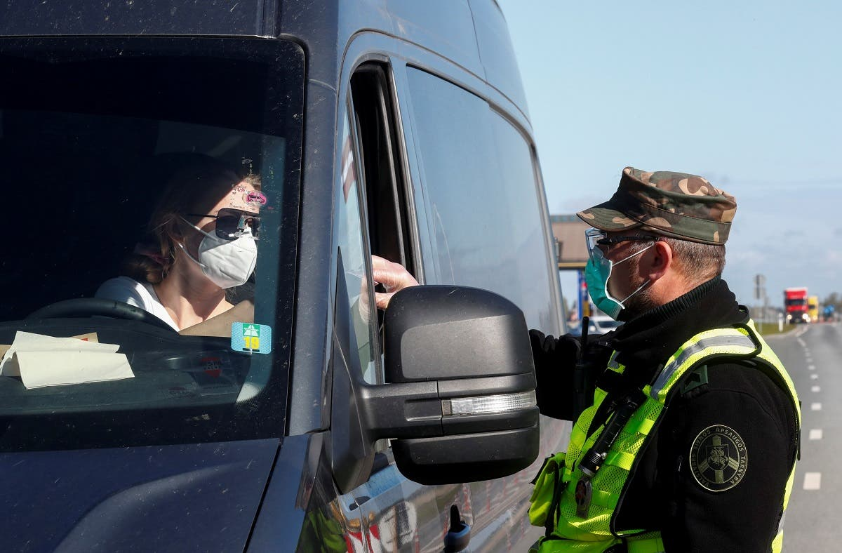 A Lithuanian border guard checks documents of a person crossing the Latvian-Lithuanian border, as travel restrictions for residents are lifted during the coronavirus outbreak, in Salociai border crossing point, Lithuania May 15, 2020. (Reuters)