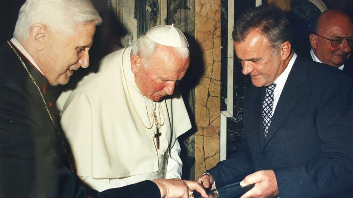Pope Benedict XVI , left, shows documents to Pope John Paul II center, as Hubert Gschwendtner, mayor of Marktl, looks on in Marktl. (File Photo: AP)