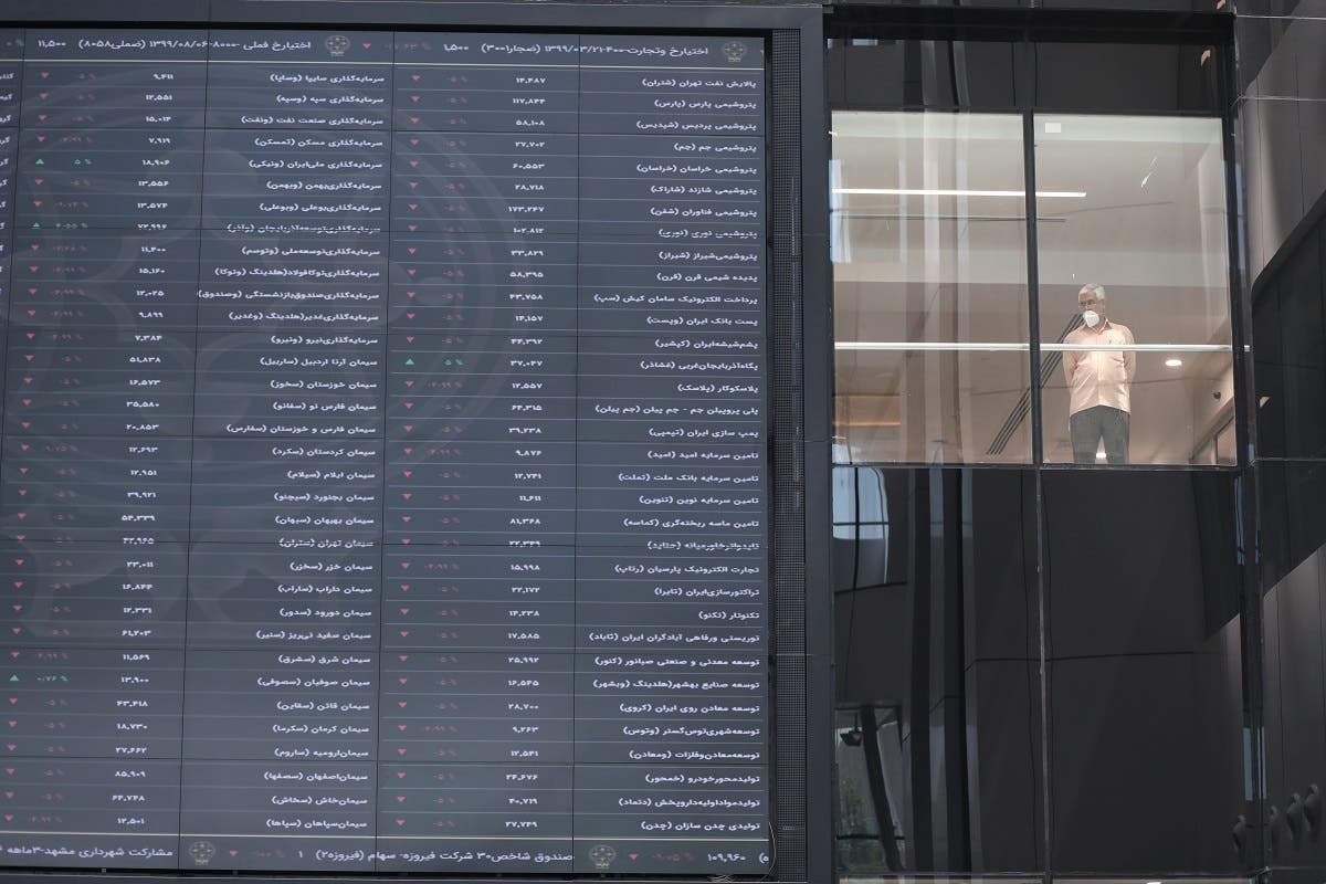 A stock market employee wearing a protective face mask stands beside an electronic board showing stock prices at Tehran Stock Exchange in Tehran, Iran, May 12, 2020. (Reuters)