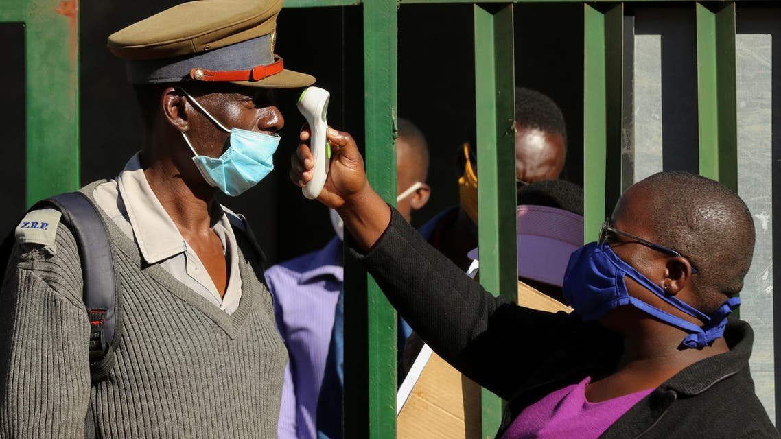 A person checks a policeman's temperature during a nationwide lockdown to help curb the spread of the coronavirus in Harare, Zimbabwe, on May 14, 2020. (Reuters)