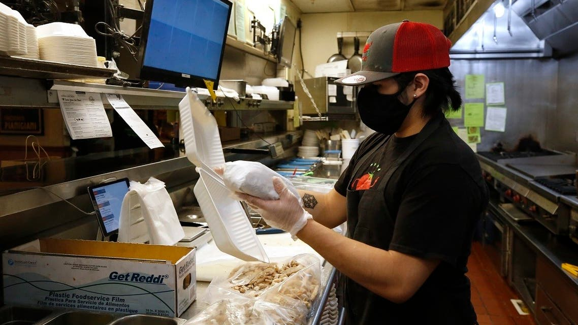 Matthew Sargosa places a sandwich in a takeout container at Dancing Tomato Caffe in Yuba City, Calif., Tuesday, May 12, 2020. (AP)