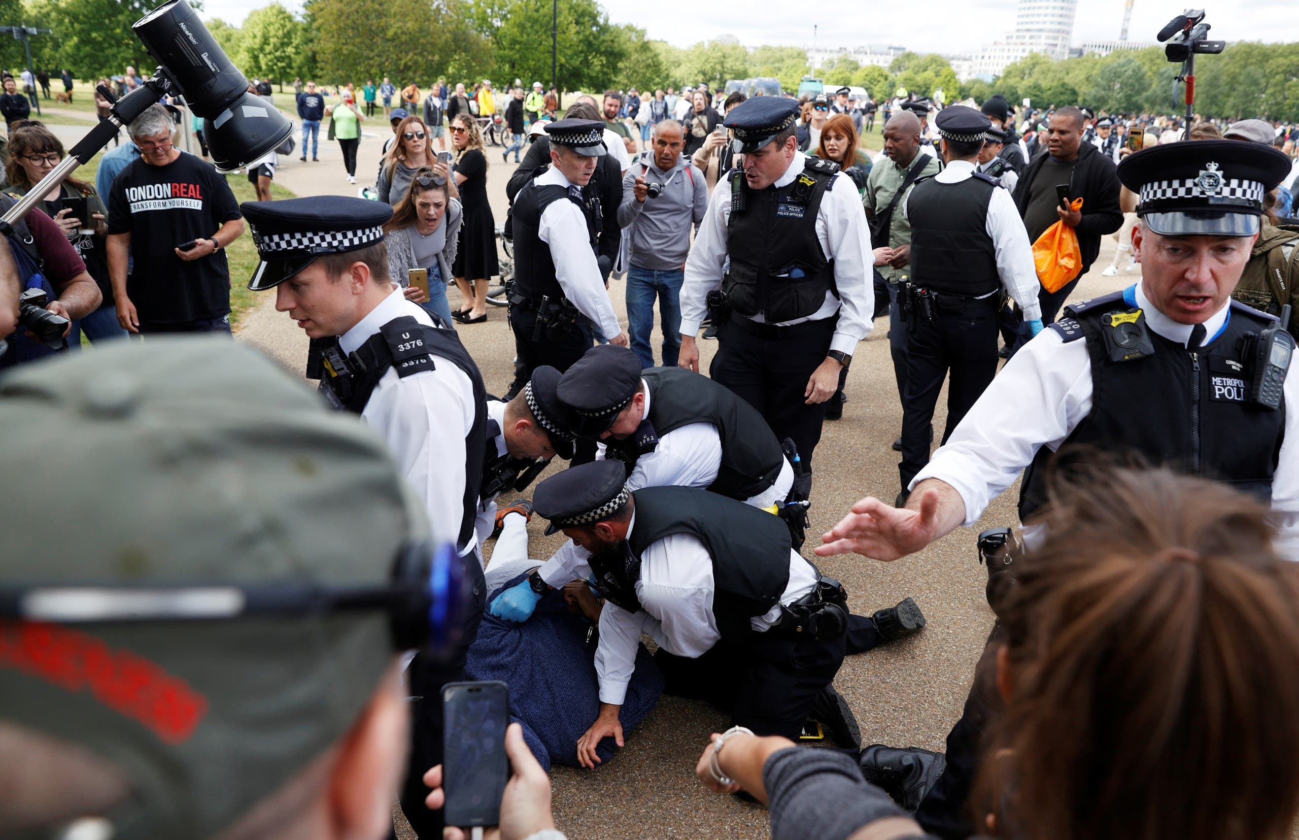 A protester is detained by police officers during a demonstration in Hyde Park, following the outbreak of the coronavirus, in London, on May 16, 2020. (Reuters)
