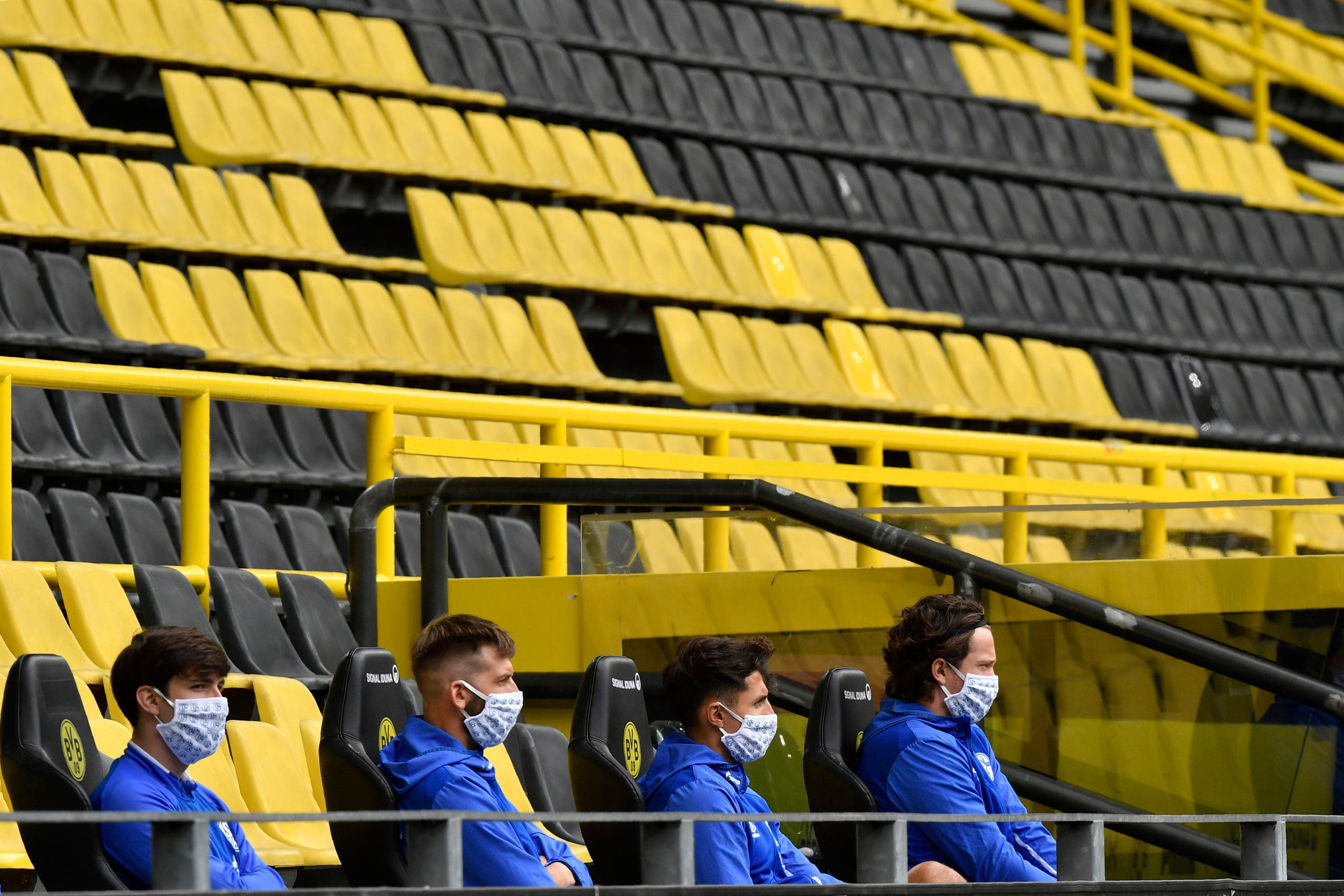 Schalke alternate players sit on the bench during the German Bundesliga football match between Borussia Dortmund and Schalke 04 in Dortmund, Germany, on Saturday, May 16, 2020. (AP)