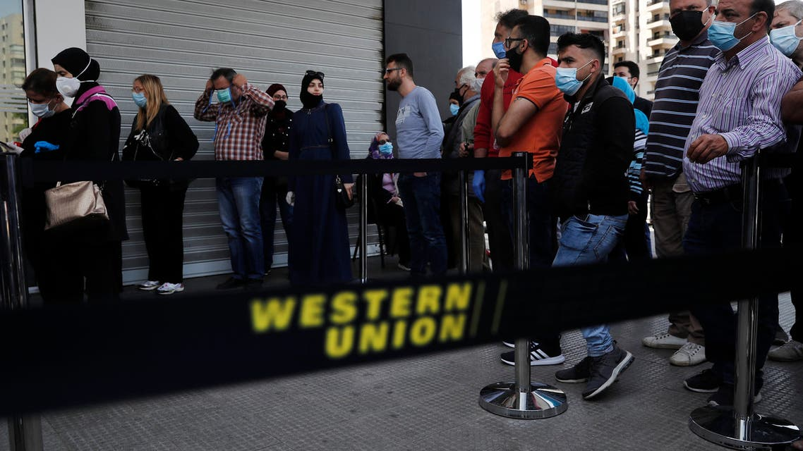 Lebanese citizens queue outside a Western Union shop to receive their money transfer in US dollar currency, in Beirut on Thursday, April 23, 2020. (AP)
