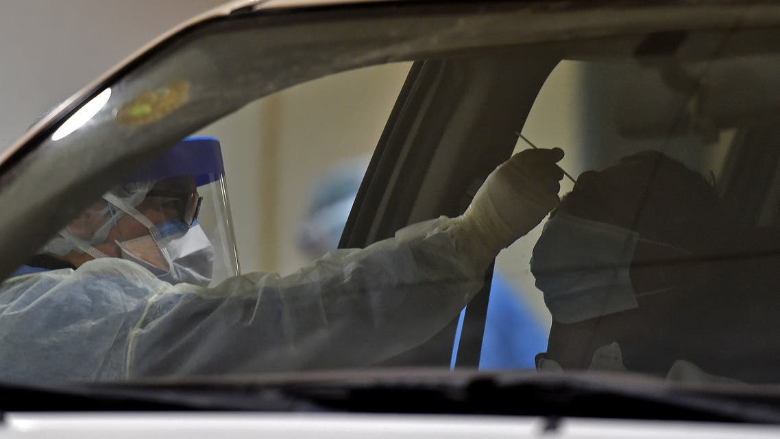 Health workers perform a nose swab test during a drive through coronavirus test campaign held in Diriyah hospital in the Saudi capital Riyadh on May 7, 2020. (AFP)