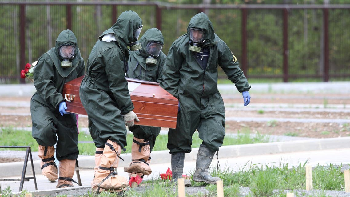 Grave diggers wearing protective suits carry a coffin during the burial of a coronavirus disease (COVID-19) victim at a cemetery on the outskirts of Moscow, Russia, May 15, 2020. (Moscow News Agency Handout via Reuters)
