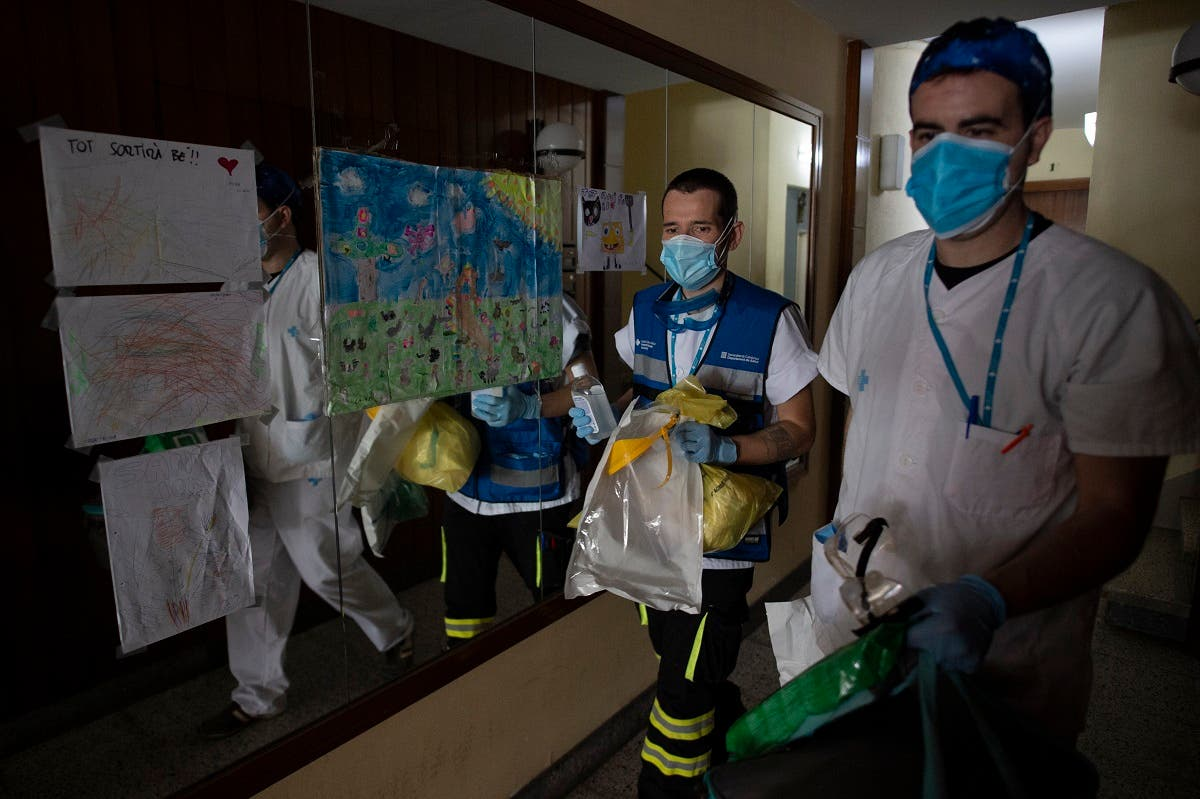 Healthcare workers leave after visiting patients at their homes in Barcelona on May 1, 2020. (AFP)