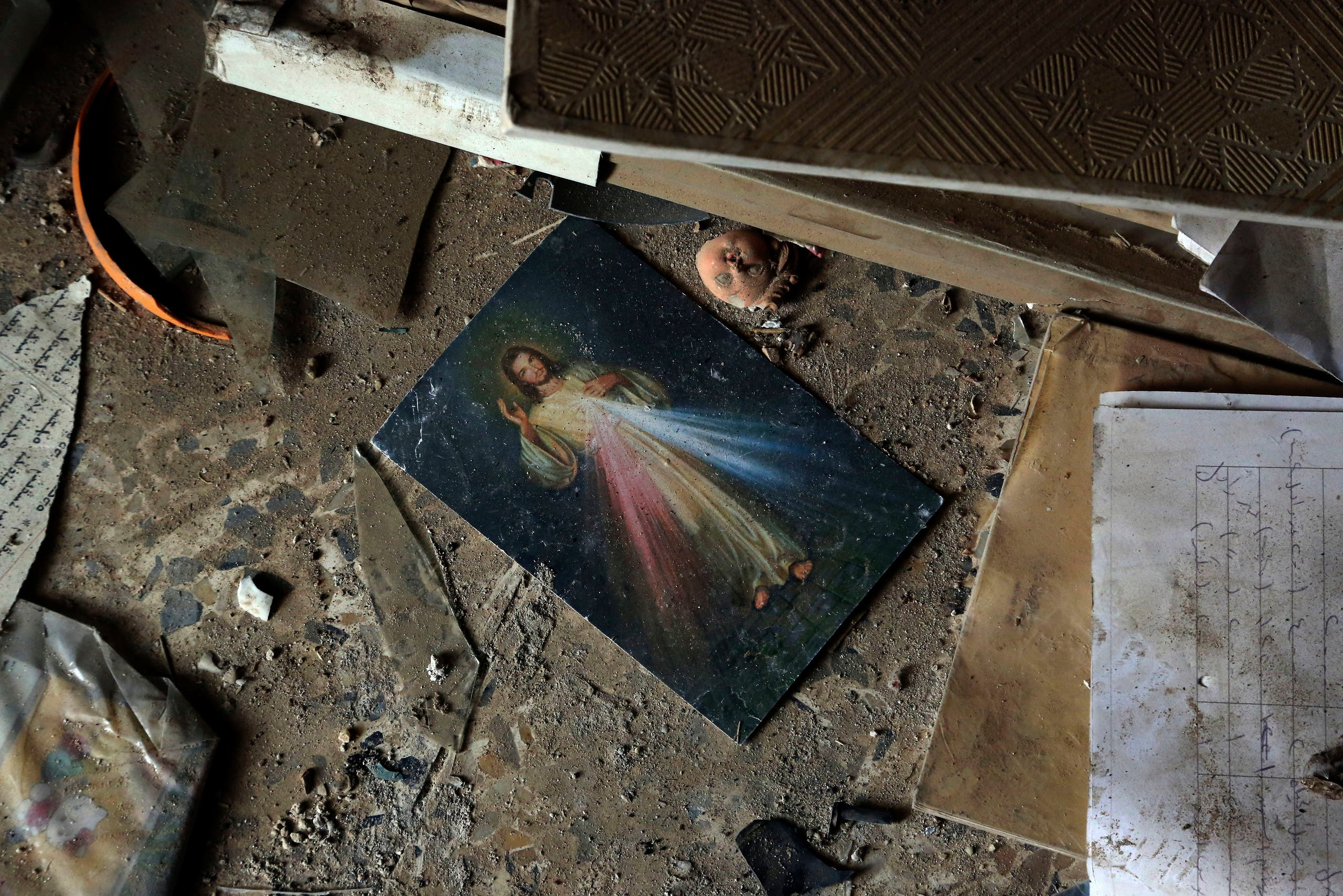 A picture of Jesus Christ lies on the ground inside a church damaged by ISIS militants during their occupation of the predominantly Christian town of Tilkaif, Iraq on Jan. 21, 2017. (AP)