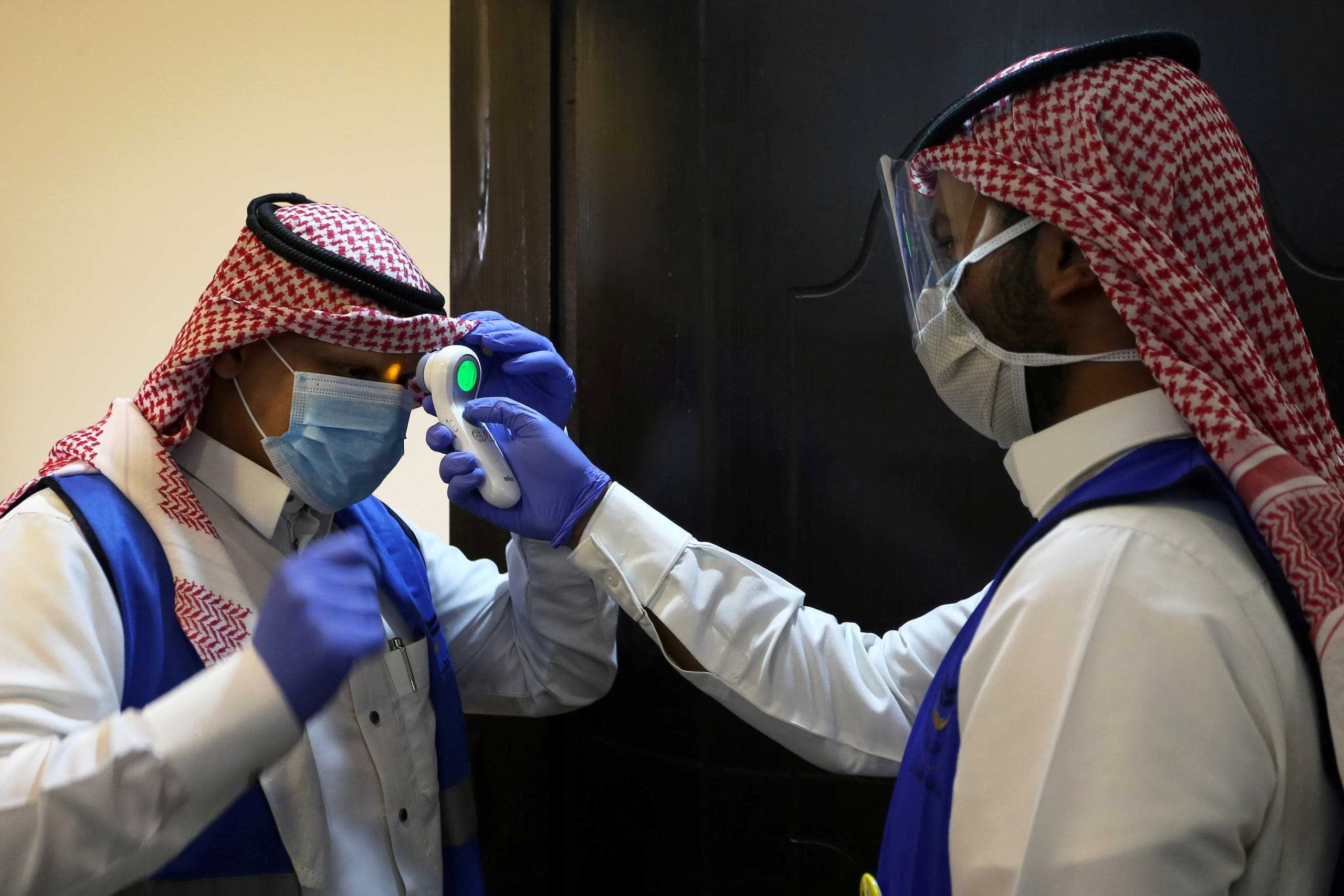 A Saudi volunteer supervisor checks the temperature of another volunteer following the outbreak of the coronavirus in Riyadh, Saudi Arabia, May 10, 2020. (Reuters)