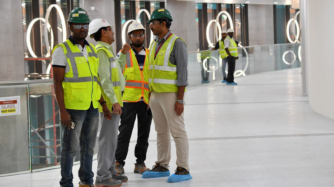 This picture taken on December 17, 2019 shows construction workers speaking together inside Qatar's new al-Bayt Stadium in the capital Doha, which will host matches of the FIFA football World Cup 2022. (AFP)