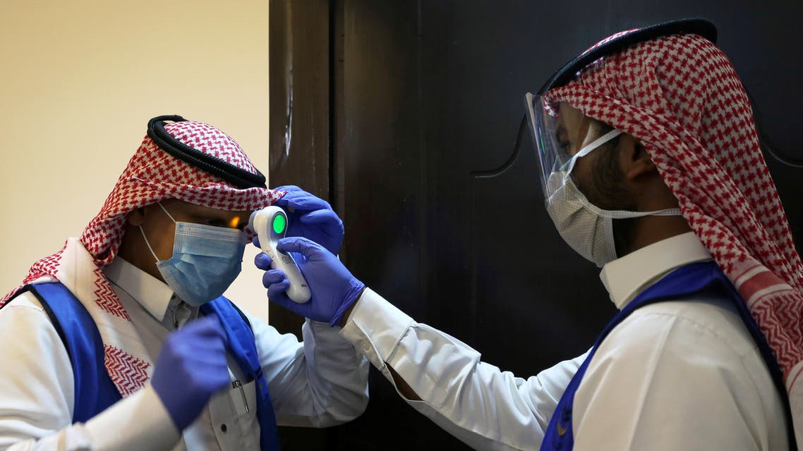 A Saudi volunteer supervisor wearing a protective face mask and gloves checks the temperature of another volunteer before preparing boxes of Iftar meals provided by a charity organisation following the outbreak of the coronavirus disease (COVID-19), during the holy month of Ramadan, in Riyadh, Saudi Arabia May 10, 2020. Picture taken May 10, 2020. REUTERS/Ahmed Yosri