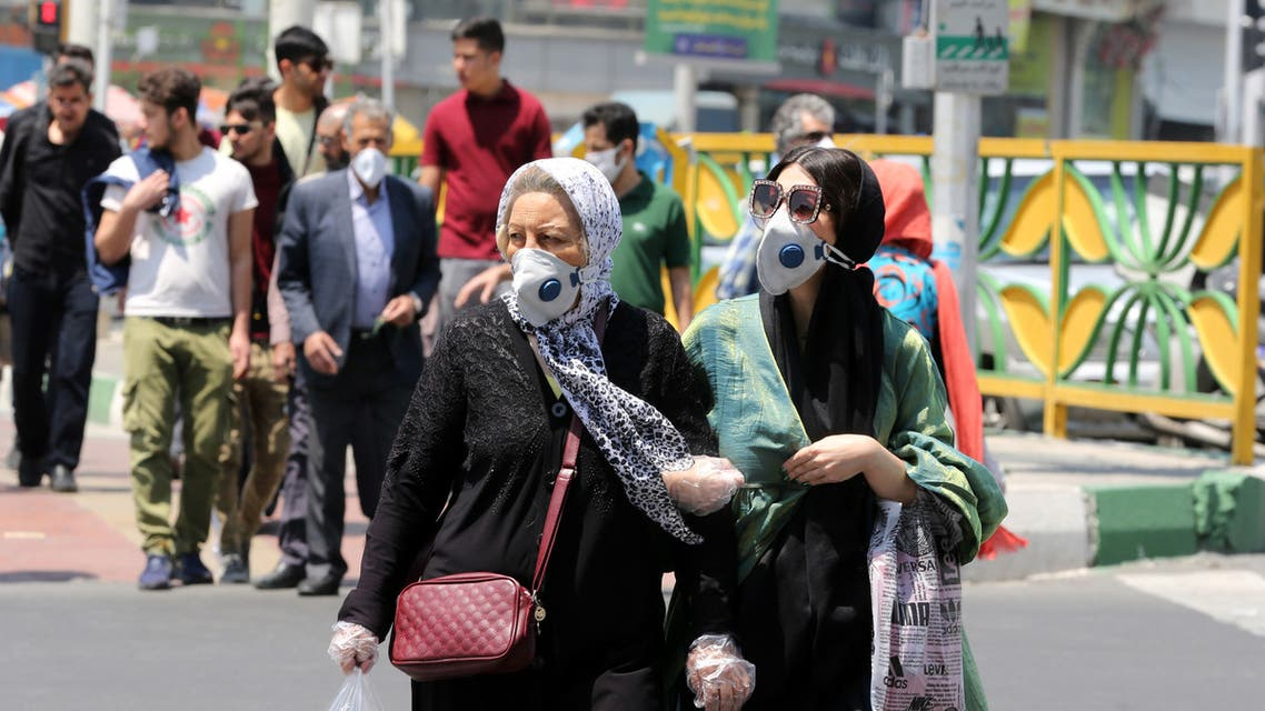Iranian women wearing protective masks amid the novel coronavirus pandemic, cross a street in the capital Tehran, on May 09, 2020. (AFP)