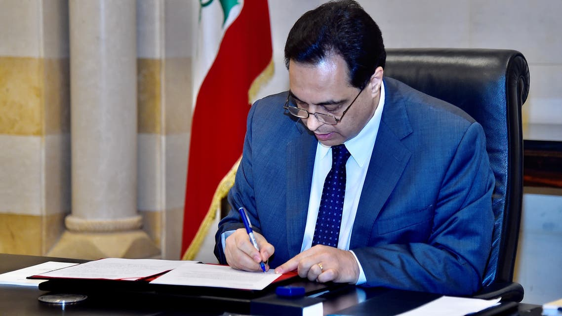 Lebanon's Prime Minister Hassan Diab signs a request for assistance from the International Monetary Fund at the government palace in Beirut, Lebanon May 1, 2020. (Reuters)
