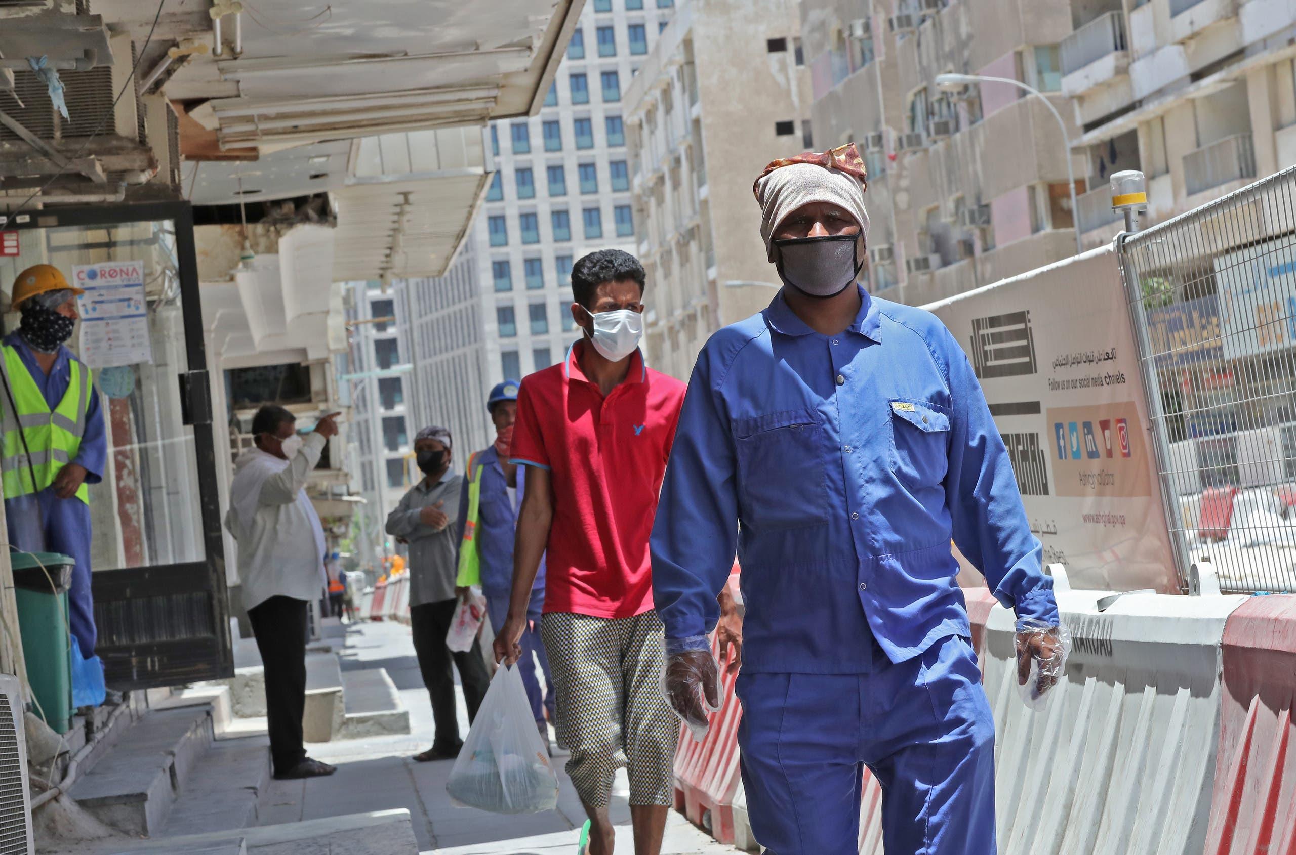 عمال يضعون الكمامات في شوارع الدوحة