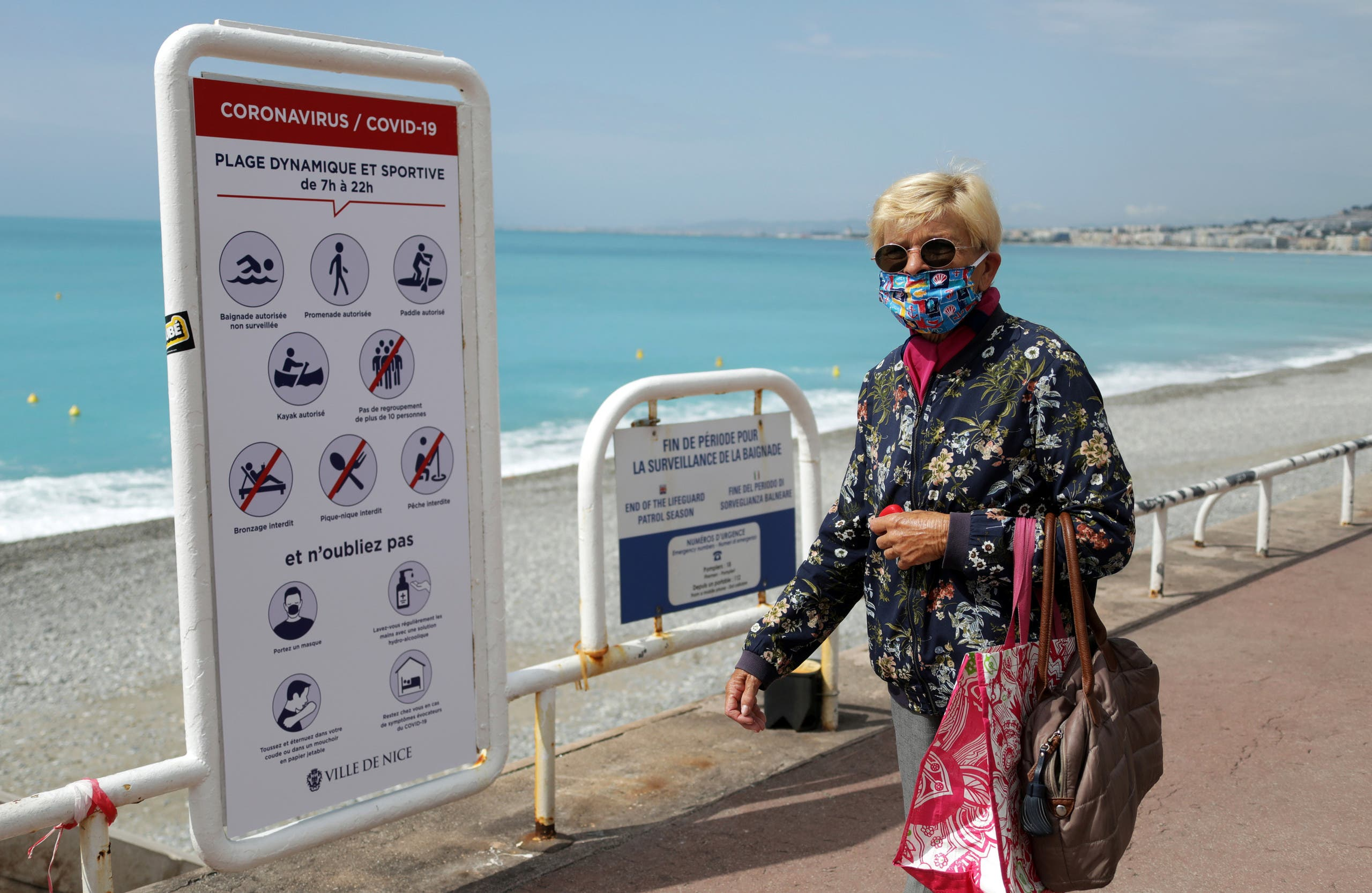 A woman, wearing a protective face mask, walks past a sign reading informations about the safety restrictions at the entrance of a beach on the Promenade des Anglais in Nice on May 16, 2020. (Reuters)
