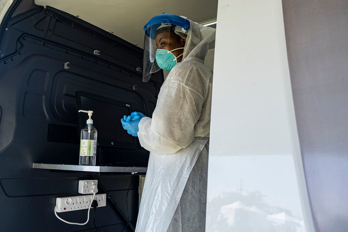 A health worker disinfects her hands as she readies herself for the next patient to be tested at a temporary coronavirus testing station in Diepsloot, Johannesburg on May 8, 2020. (AFP)