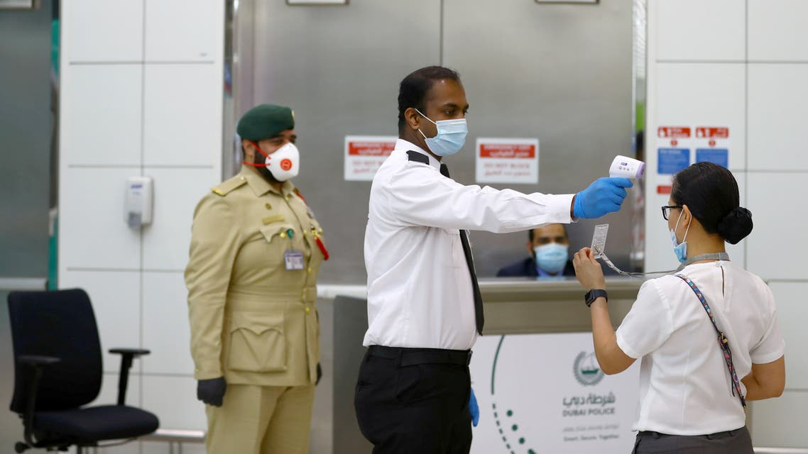 A security man takes temperature of a woman amid the outbreak of the coronavirus disease (COVID-19) at Dubai International Airport, UAE April 27, 2020. Picture taken April 27, 2020. REUTERS/Ahmed Jadallah