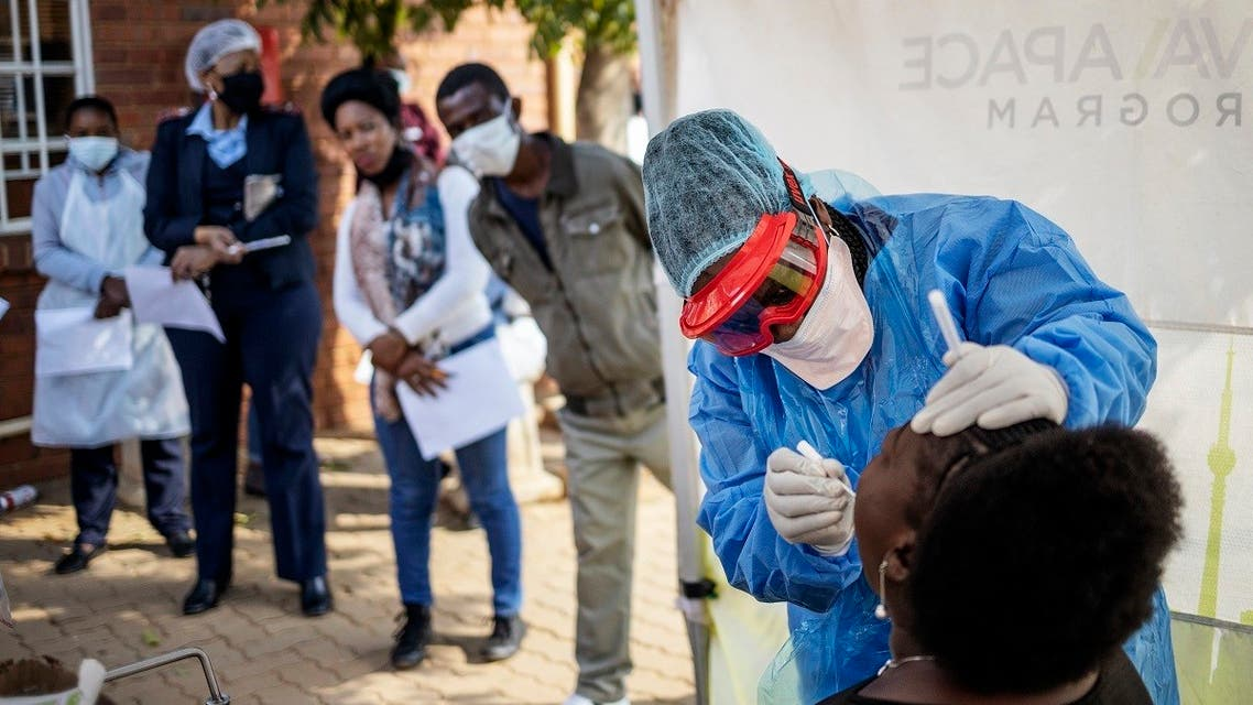 Doctors Without Borders (MSF) nurse Bhelekazi Mdlalose (2nd R) performs a swab test for COVID-19 coronavirus on a health worker at the Vlakfontein Clinic in Lenasia, Johannesburg, on May 13, 2020. (AFP)