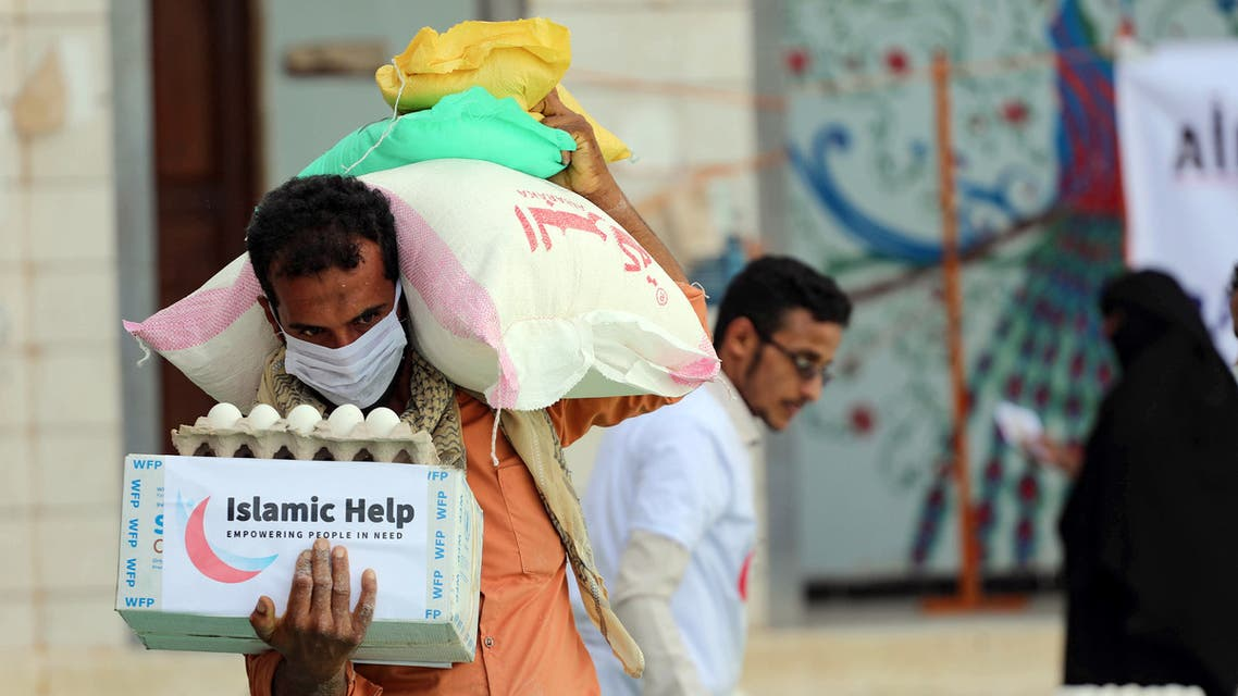 A man wearing a protective mask receives humanitarian aid in Yemen's third city of Taez, on May 8, 2020, amid the novel coronavirus pandemic crisis. (AFP)