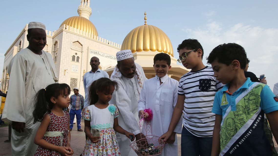 Muslim children distribute chocolates at the end of the morning Eid al-Adha prayer outside a mosque in the Omani capital Muscat on September 12, 2016. (AFP)