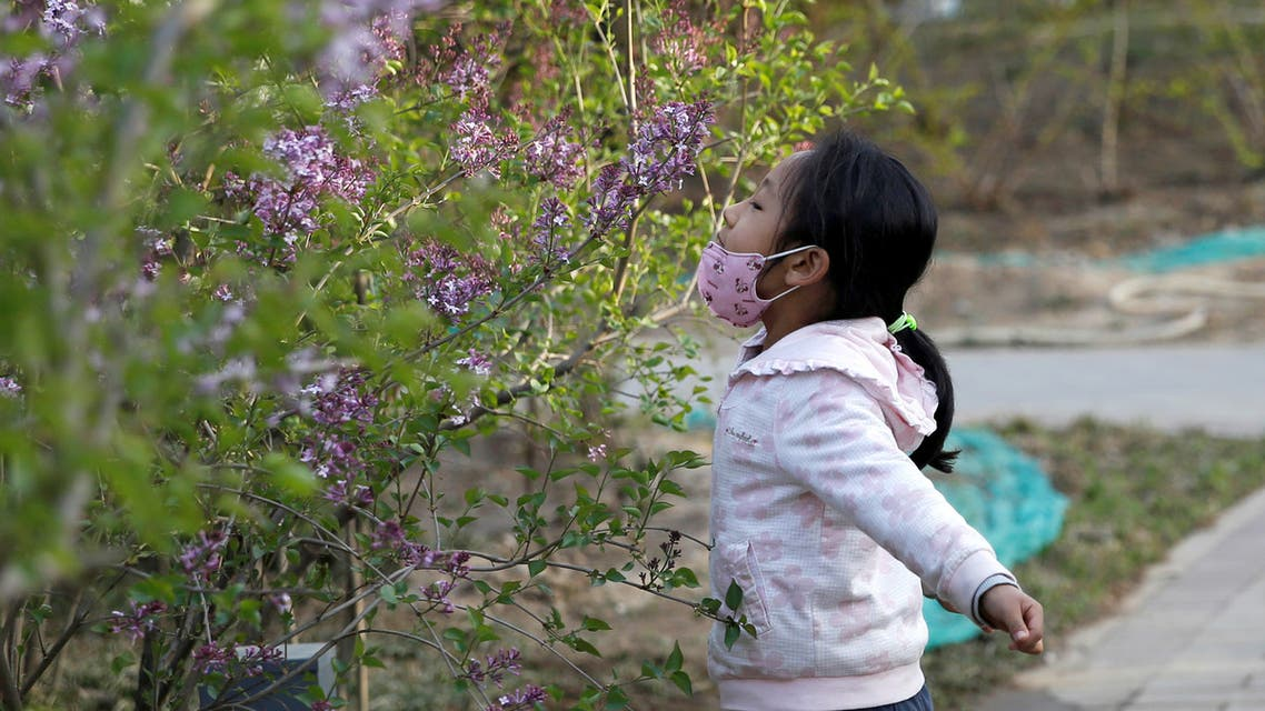 A girl smells blooming flowers at a park as she removed her protective face mask, as the country is hit by an outbreak of the novel coronavirus disease (COVID-19), in Beijing. (Reuters)